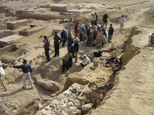 "One of the Late Period (664-525 BCE) coffins in situ after clearing. In the distance you can see the mastaba (Arabic word for ""bench"") tombs belonging to high officials of the King"