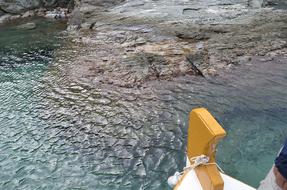 The boat drifting just metres away from the rock platform
