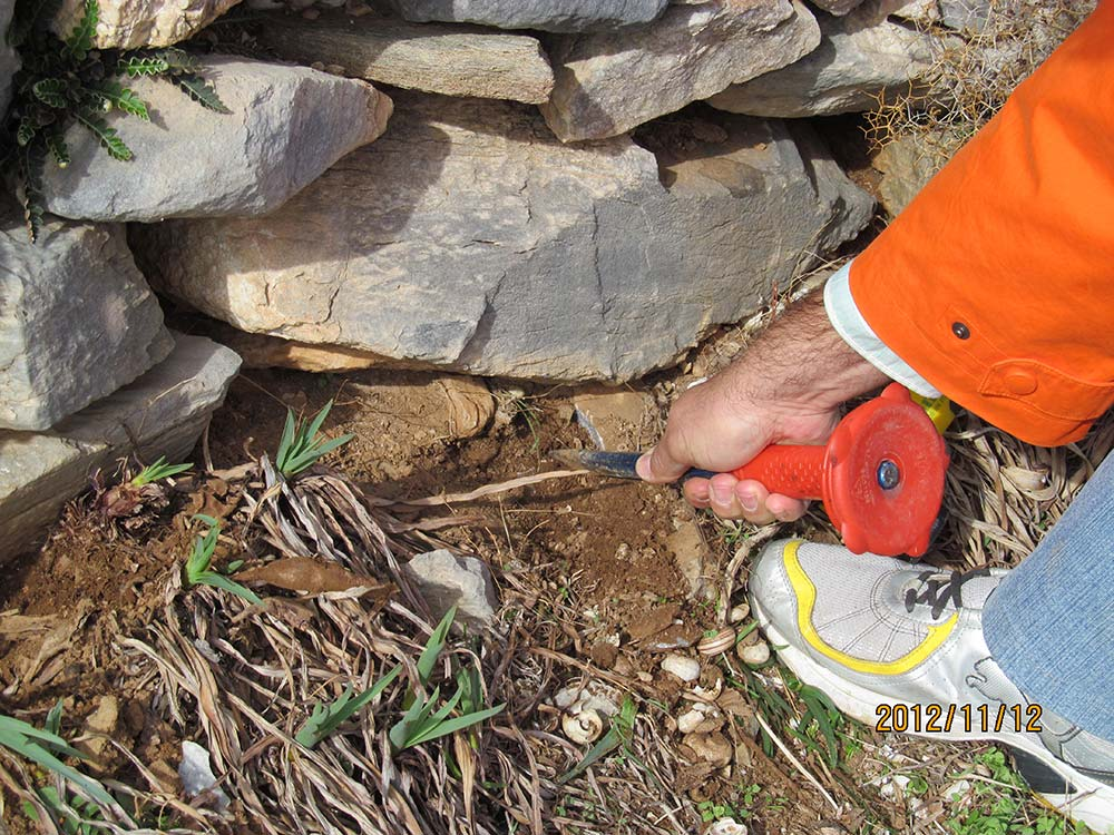 Ioannis Liritzis using a chisel to take a small rock sample