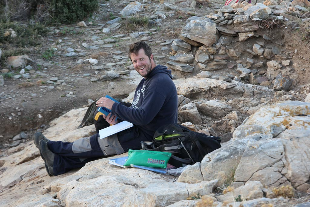 Hugh Thomas sitting on bedrock in Excavation Area 3 examining the Munsell Chart for information about soil colour