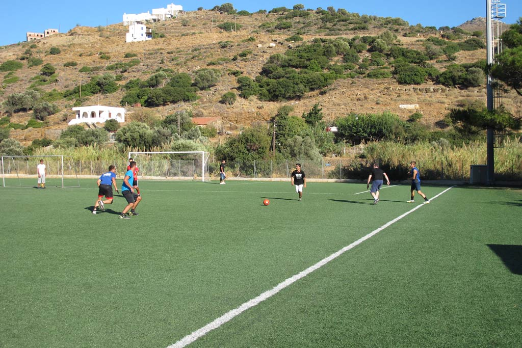 Sami Beaumont-Cankaya is after the ball. You can see one of the high hills of Batsi in the background. There are goats grazing on the hill