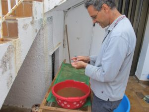 Stavros cleaning an artefact with a wet toothbrush