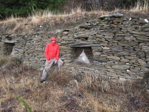 Paul Donnelly, in front of a stone wall containing beehives