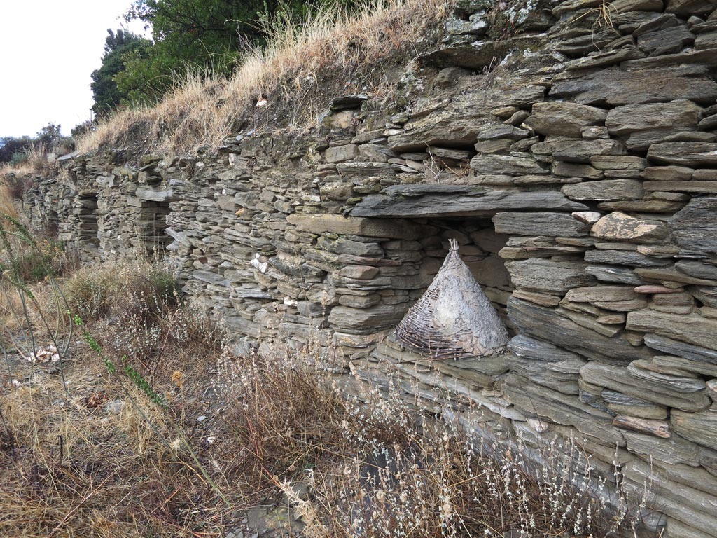 A conical beehive set into a dry stone wall just south of Zagora