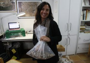 Melanie Fillios holding a bag of bones which she is about to sort