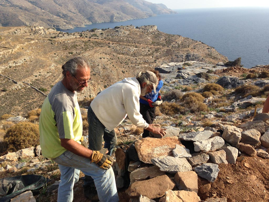 Steve Vasilakis and Kostis Fragiadakis place stones on a protective wall they are building around a trench