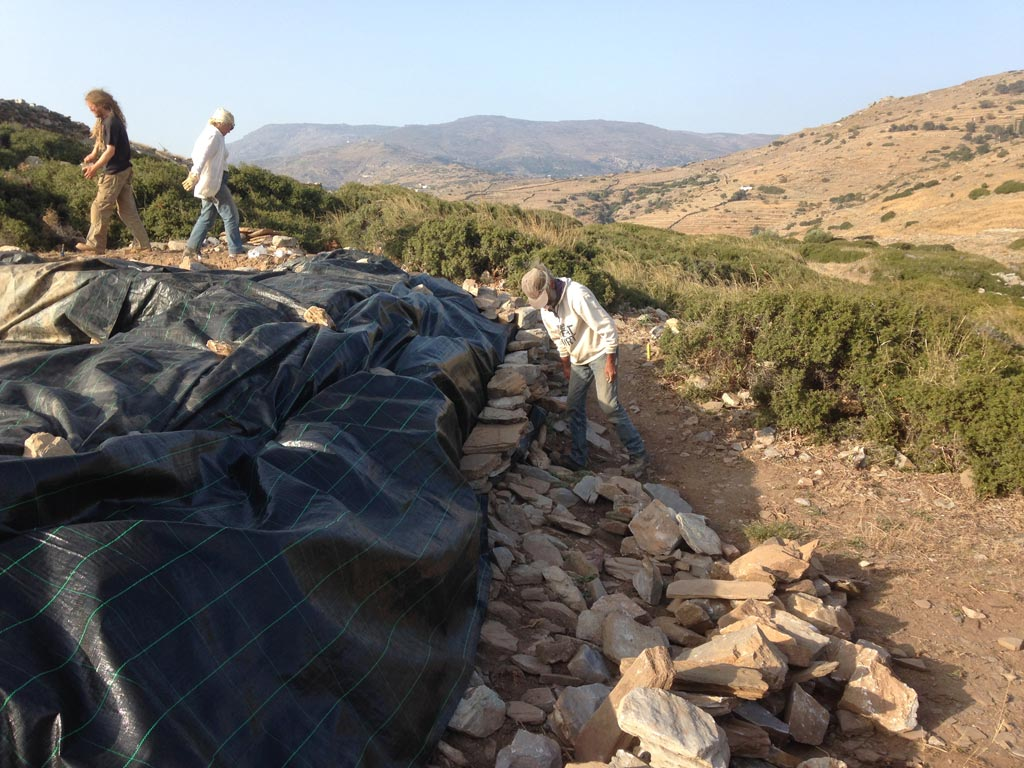 Callum Ferrell, Meg Miller and Kostis Fragiadakis select and place stones onto the geo-textile to protect the trench