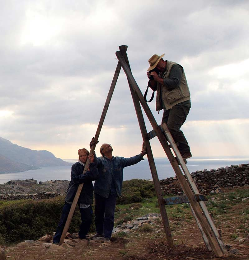 Bob Miller taking a photograph from an improvised ladder which is supported by Kristen Mann and Steve Vasilakis