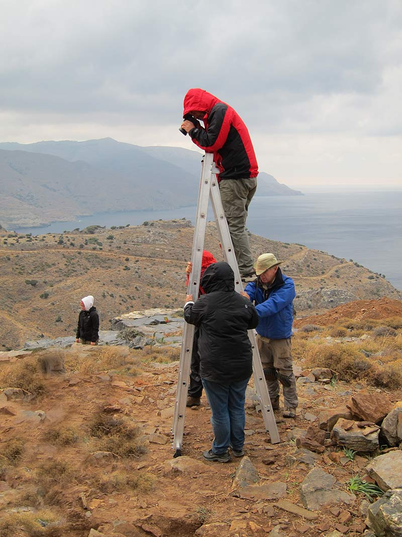 Bob Miller taking a high-angle photograph from a ladder at Zagora. It was very windy this day, so several people were required to steady the ladder to ensure Bob's safety
