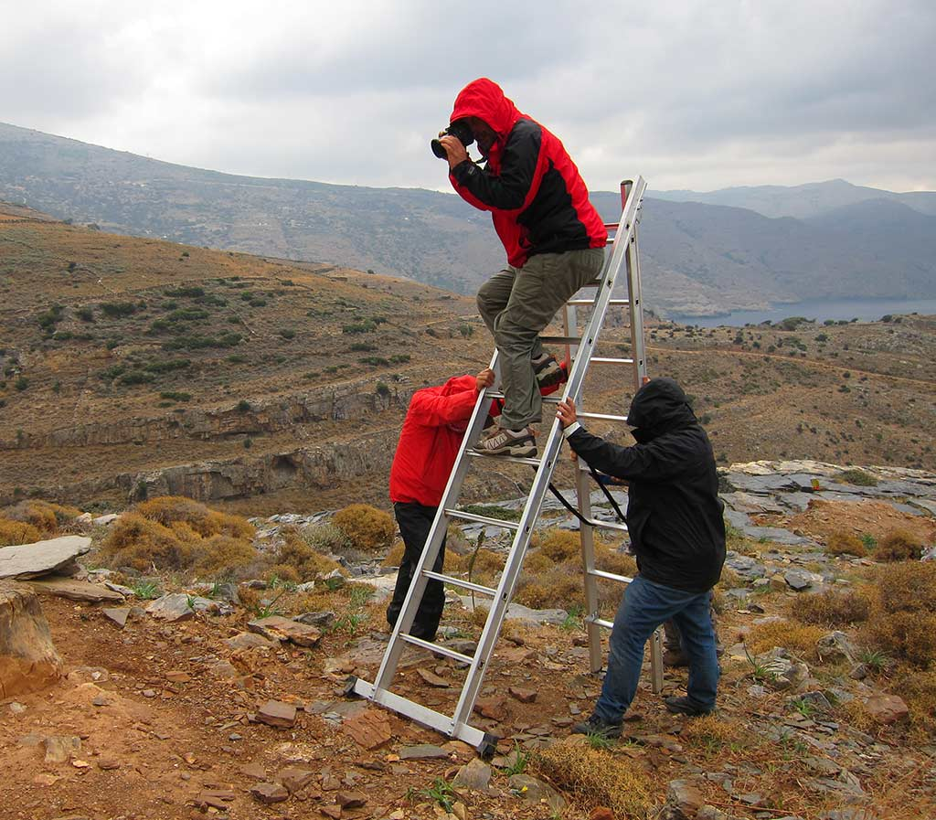 Bob Miller taking a photograph from a ladder at Zagora. The ladder is supported by Paul Donnelly and Anne Hooton